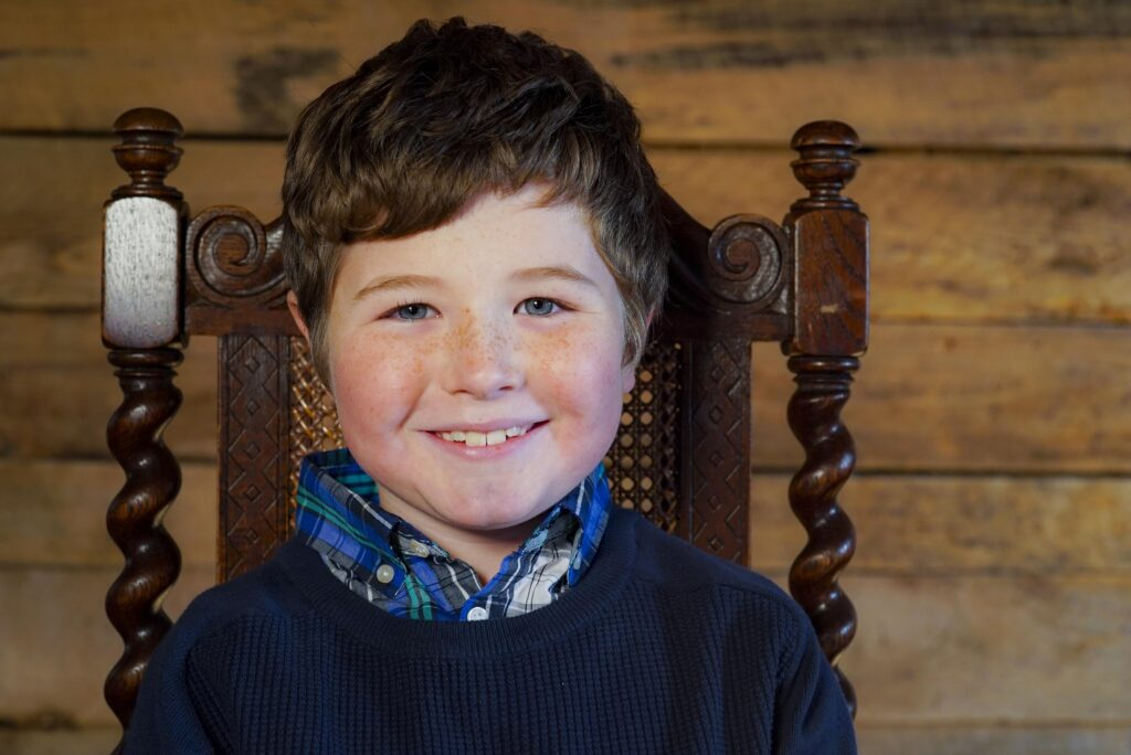 photo of a small boy sitting in a chair in a blue sweater