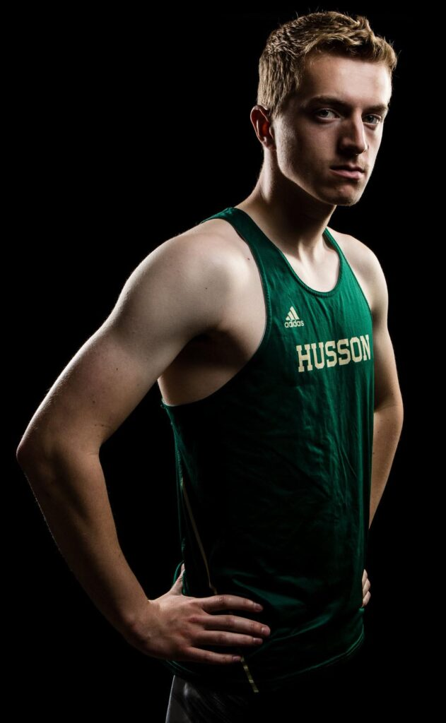 photo of man standing in green husson athletics shirt