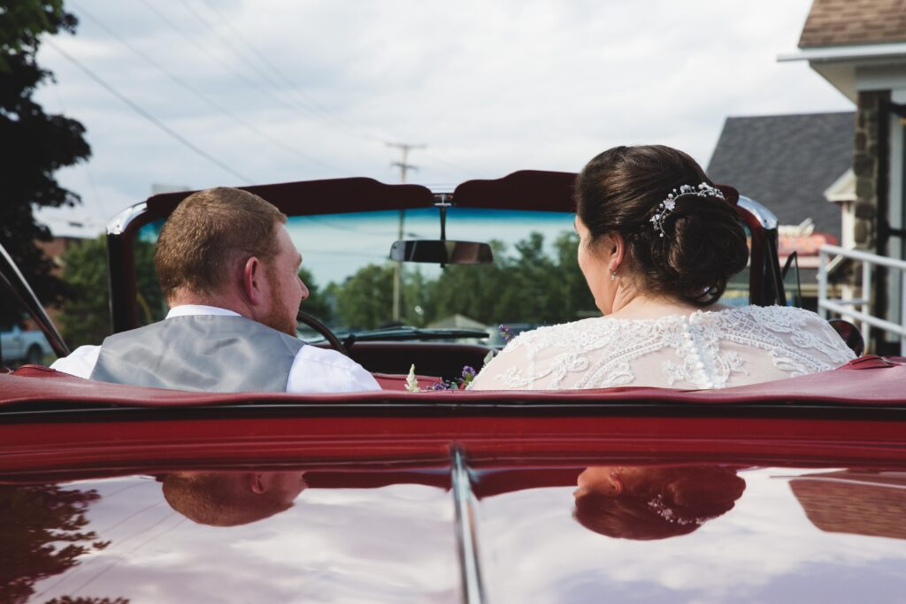 photo of bride and groom driving away in a car