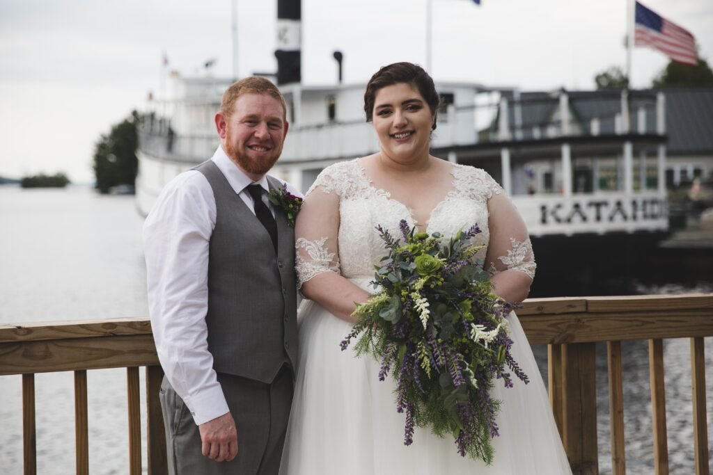 photo of bride and groom standing on a dock in front of the katahdin cruises boat