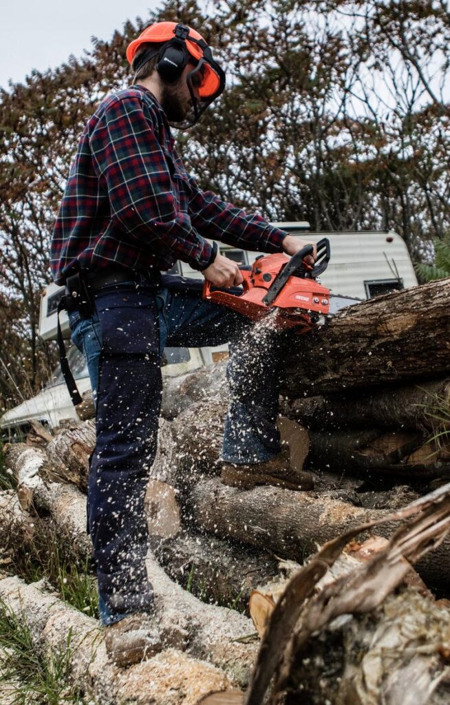 photo of a man wearing safety equipment and cutting logs with a chainsaw