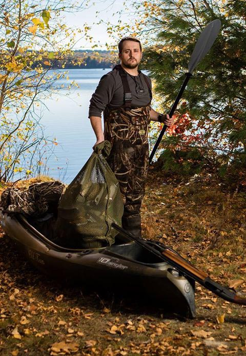 photo of man in camouflage gear holding an oar standing next to canoe and gun