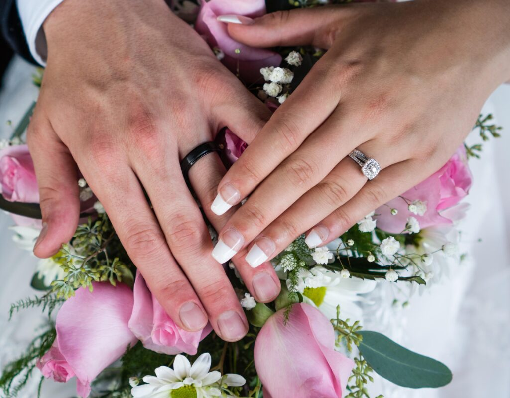 photo of bride and groom hands over flowers with wedding bands