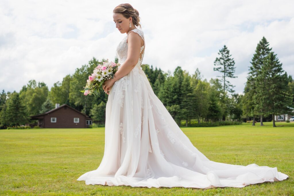 photo of bride holding bouquet of flowers standing in field outside