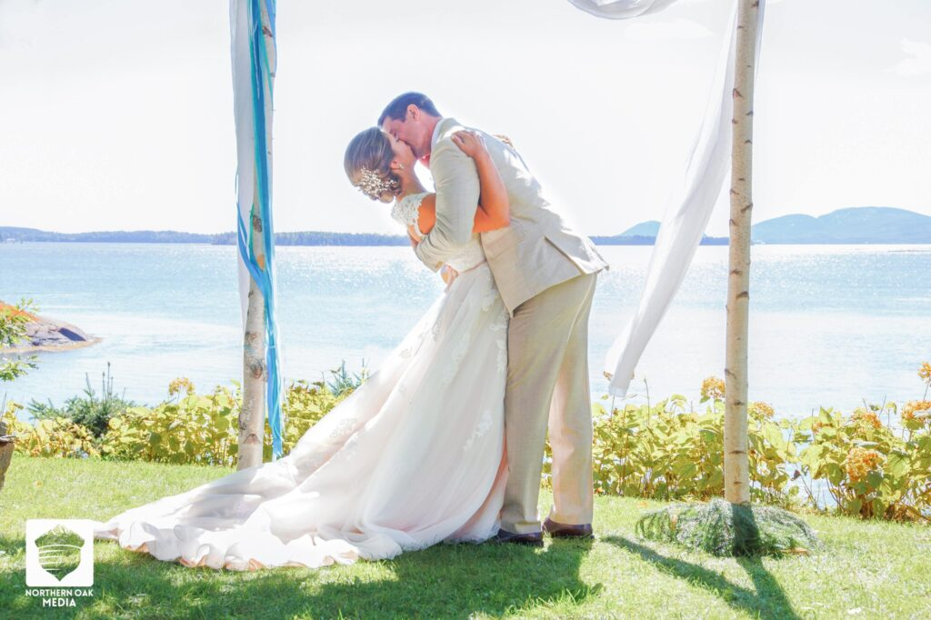 photo of bride and groom kissing under arch outside overlooking lake