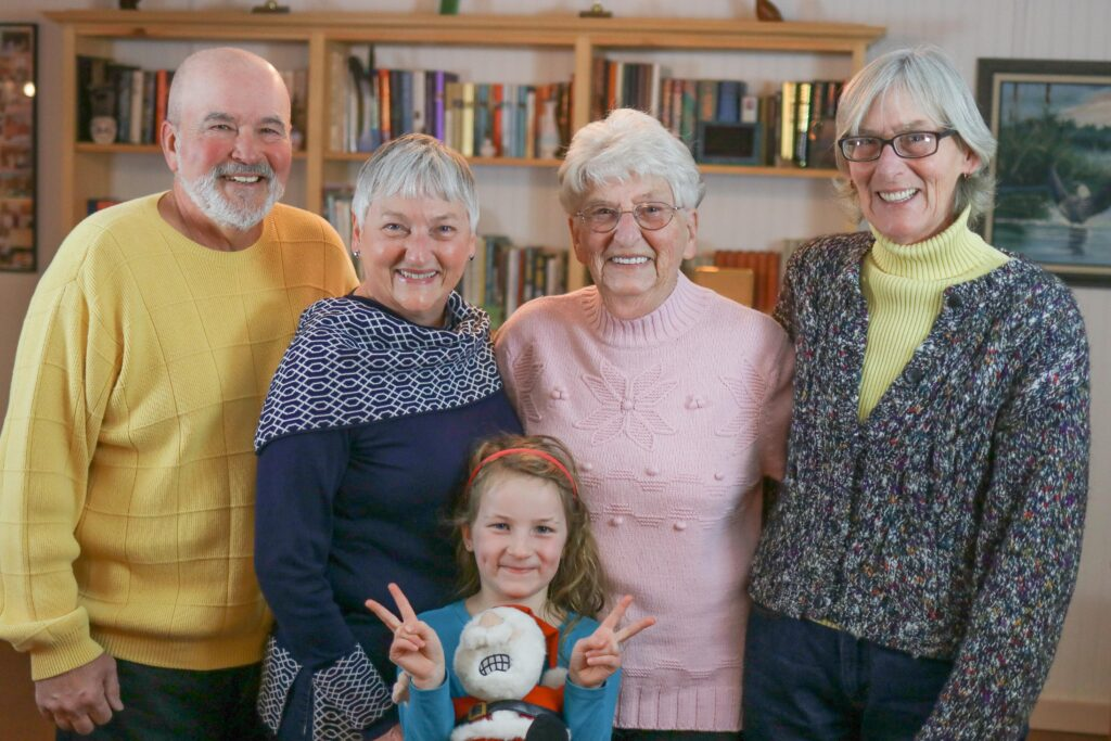 photo of four senior citizens and one little girl standing together in front of a bookcase
