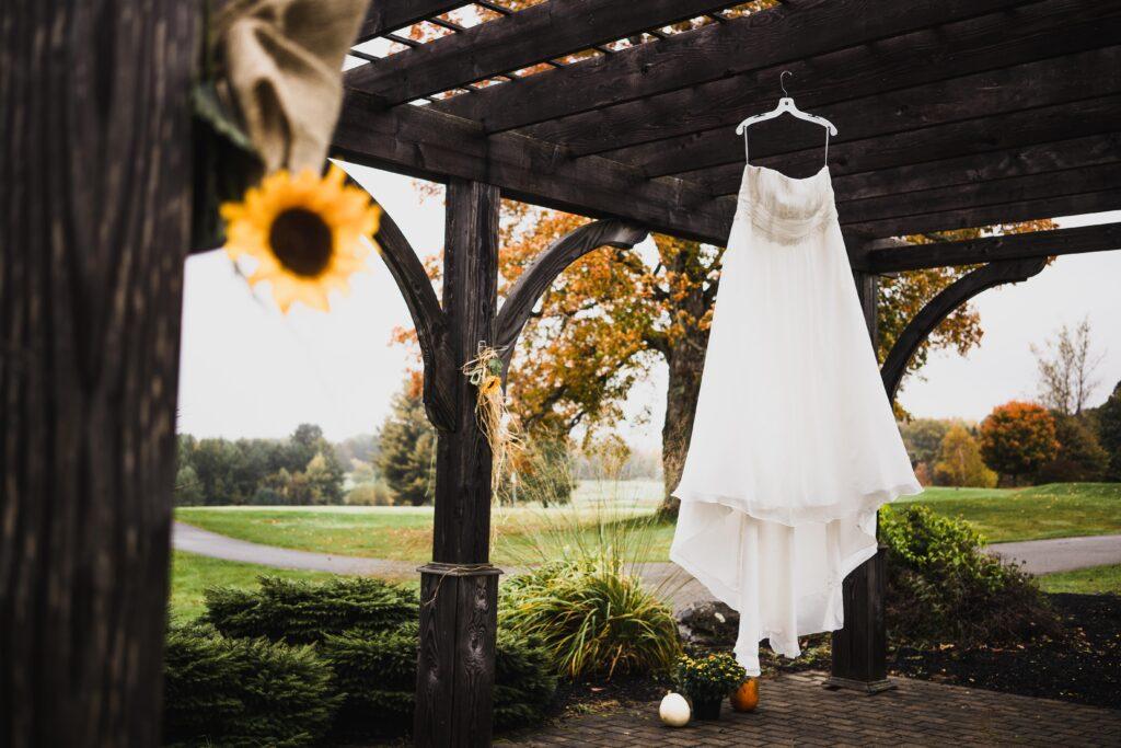 photo of wedding dress on a hanger in outside gazebo