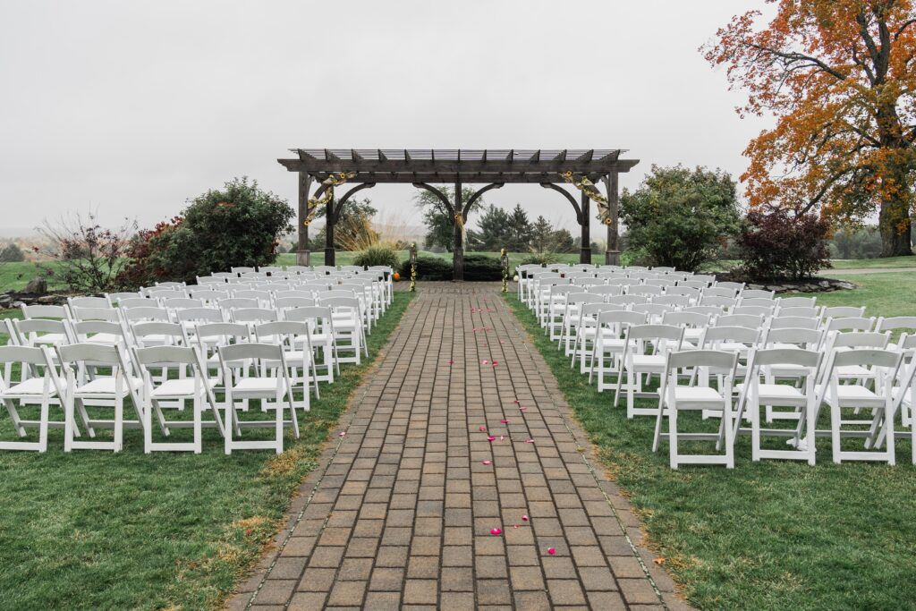 photo of wedding ceremony venue outside with arches and folding chairs