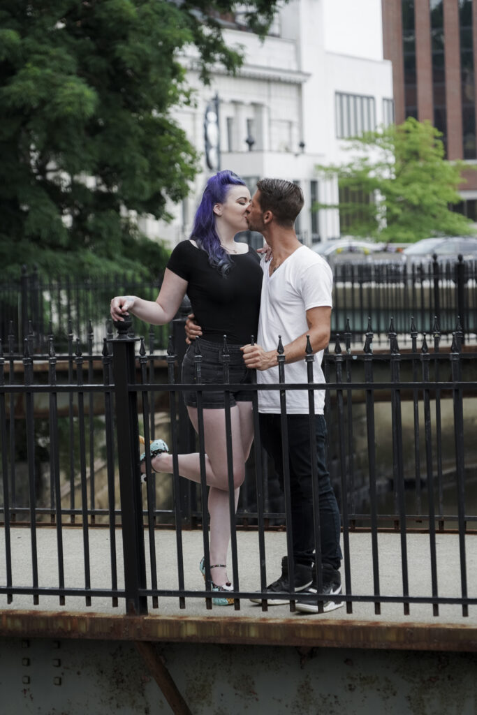 photo of a man and woman kissing on a foot bridge