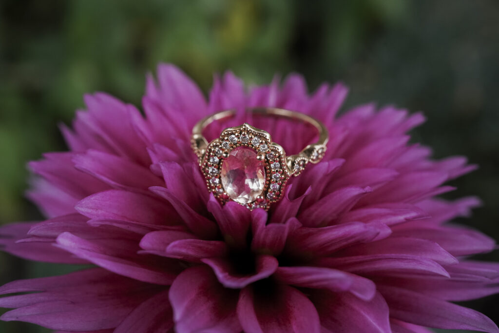 up close photo of an engagement ring on a flower