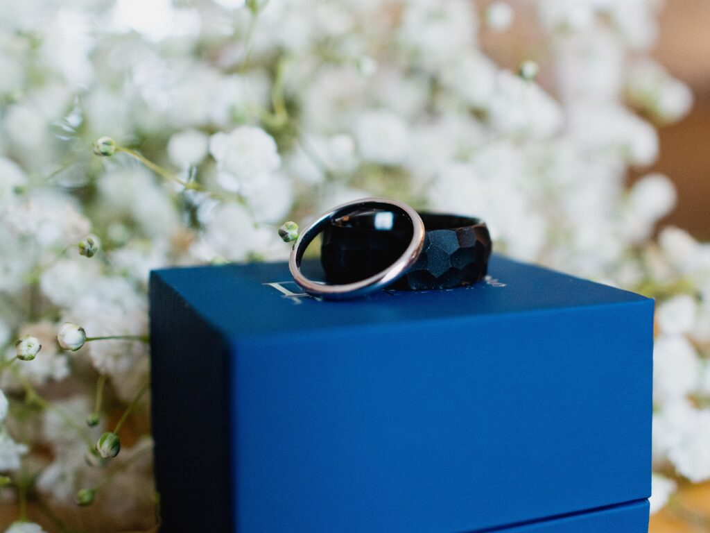 up close photo of wedding rings sitting on a blue box