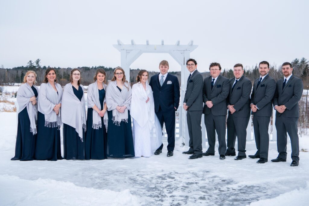 photo of bride and groom standing outside with wedding party in winter